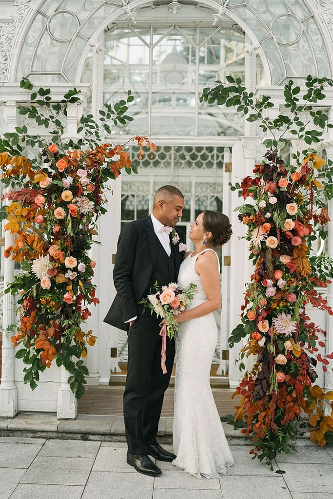 Bride and Groom with Autumnal Deconstructed Flower Arch