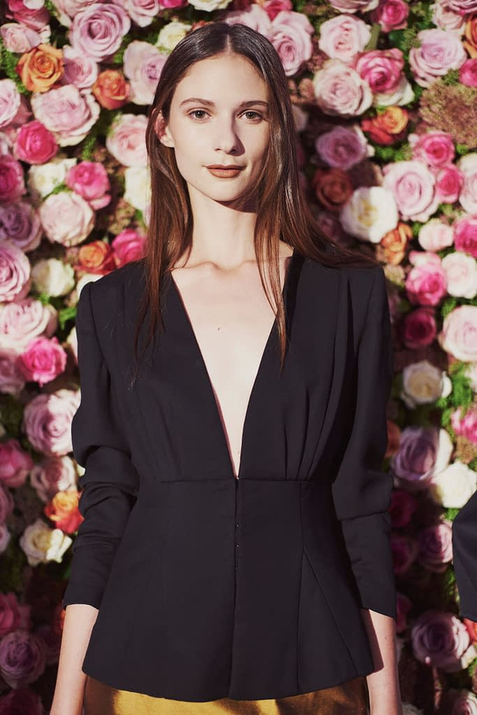 Model standing next to Flower Wall